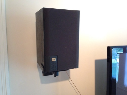 JBL J520m speaker wall mounted with grill cover next to TV