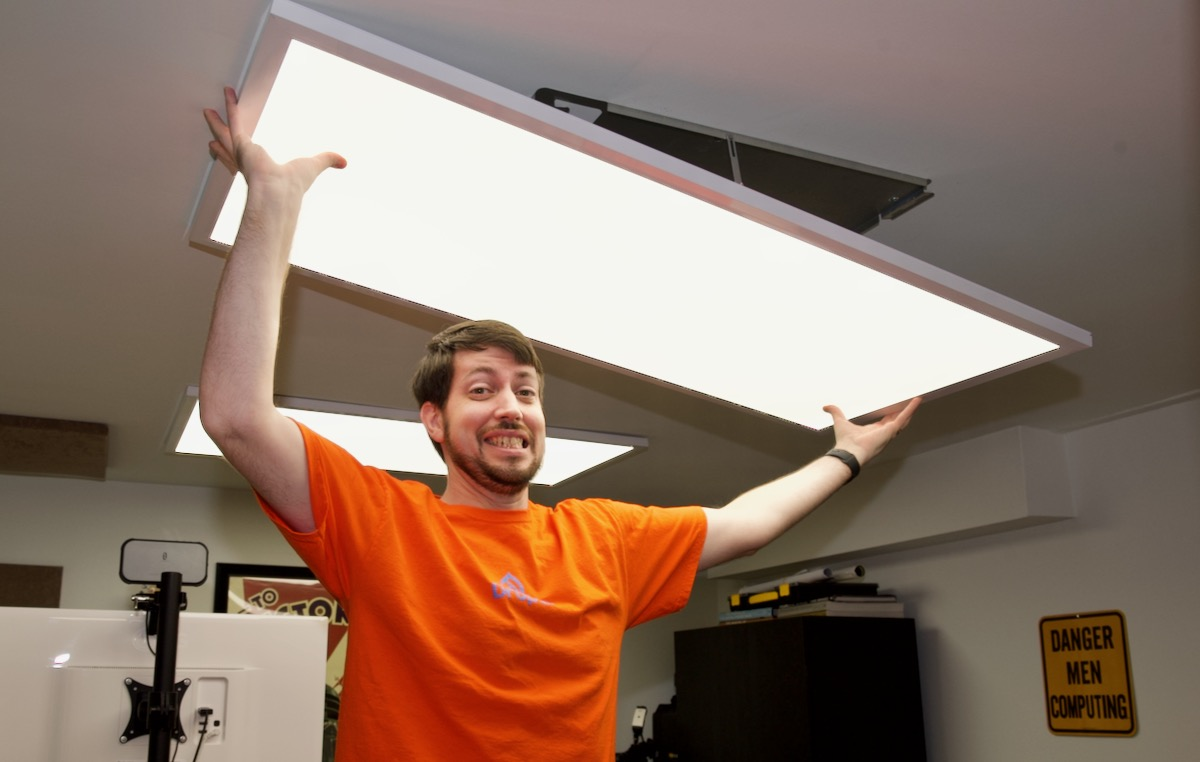 Jeff holding overhead light in office
