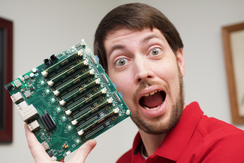Jeff Geerling acts surprised for a YouTube thumbnail pic, while holding a Turing Pi